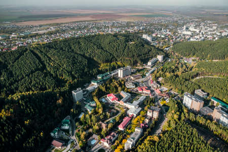 Top view of the resort town Belokurikha. Bird's-eye view of the houses among the forests on the slopes of the mountains. Aerial view of a small town in the Altai territory 免版税图像