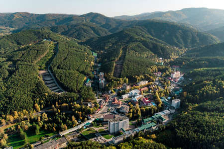 Top view of the resort town Belokurikha. Bird's-eye view of the houses among the forests on the slopes of the mountains. Aerial view of a small town in the Altai territory Reklamní fotografie