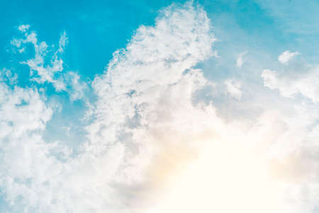 sky with clouds and sun. ecrice the rays of the sun shining through the feathery white clouds in the blue sky. Beautiful background.
