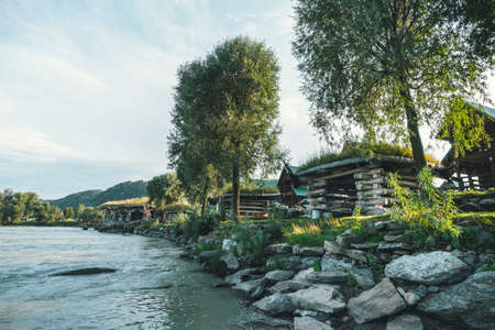 Small log houses for outdoor recreation are located on the river Bank. Hunting ground. Tourist base near the water. 免版税图像