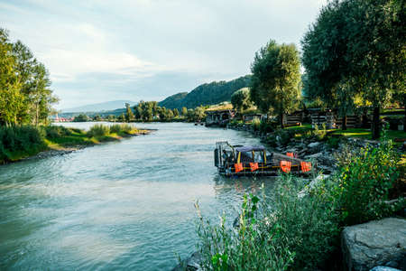 Hovercraft boat in the river Katun Altai Krai. Over turquoise blue waters of the Katun river along the village