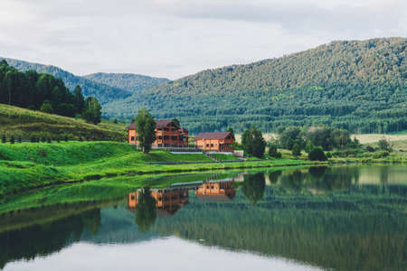Beautiful landscape of mountains and lakes. The log house is reflected in the clear water. Tourist base in the mountains. Country house for environmentally friendly outdoor recreation Stock fotó