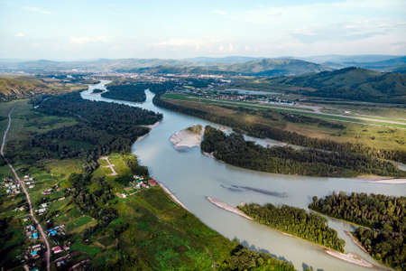 Village in Russia, Altai Mountains, houses and Katun River. Top view of the mountain river in the Altai mountains and the village of Aya. Altai territory.