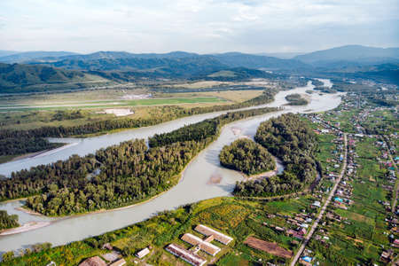 Aerial view of Katun river, in Altai mountains. Top view of the mountain river in the Altai mountains and the village of Aya. Altai territory.
