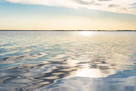 reflected sun rays on sea water. Glare on the water in the form of stars. Natural abstract sea water background.