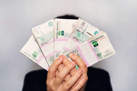 a lot of money in the hand of a young businessman on a blue background. A stack of banknotes of Russian rubles with a face value of 1000 rubles. successful businessman 免版税图像
