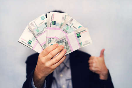 thousandth banknotes of the Russian ruble in a man's hand. male hand with a bundle of banknotes. transfer of money. thumbs up as a symbol of a successful deal.