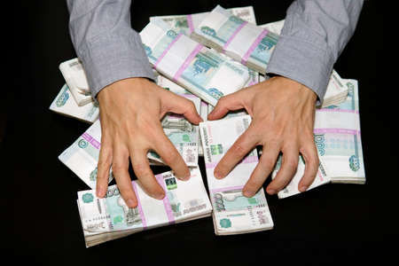 Lust for money. Large stack of banknotes, Russian rubles, banknotes 1000 rubles. hands are grabbing money. 免版税图像
