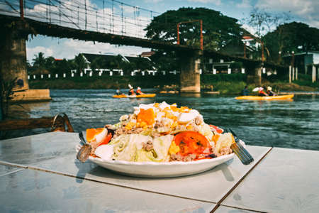 food of the national Lao cuisine a white plate on the table in the restaurant located on the Bank of the Nam Song River on which tourists float on a kayak.