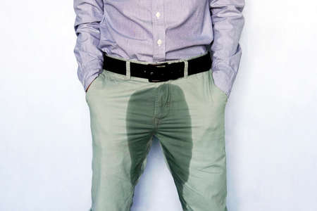 Problems with the bladder. The concept of men's health. Young man in light trousers with wet stain from urine.