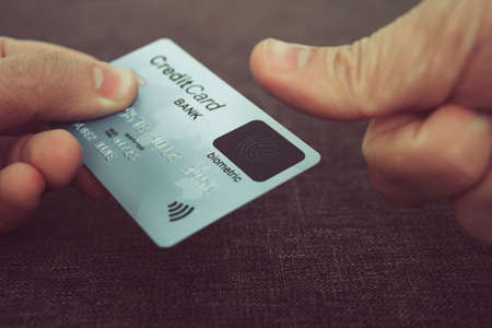 Close up of male hands holding credit card with fingerprint scanner and embedding the thumb to pay online. Concept of using biometric technology in banking. Cardholder touching his biometric card