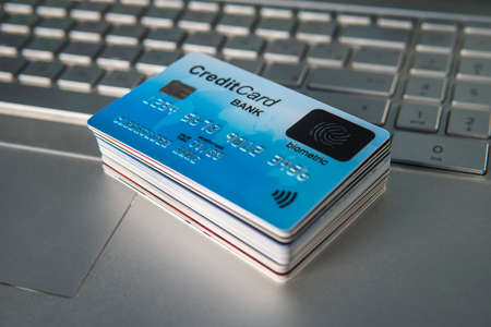 Pile of plastic credit cards on the laptop keyboard. Open access for online shopping using biometric card. Payment cards with finger sensor on the surface. Payment system of new generation. Stack Archivio Fotografico