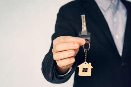 Unrecognizable businessman offering a keys, closeup shot.