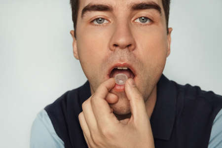 A young cute man sucks a pill from inflammation of the tonsils. Stock Photo