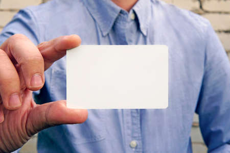Businessman in a blue shirt against a brick wall on the street in hand hold show blank white  name card