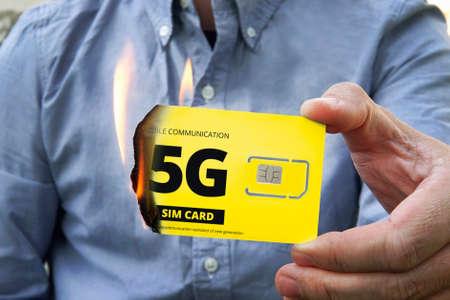 A paranoid man burns a 5G SIM card for fear of harmful radiation.