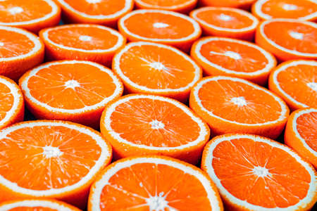 Red oranges or grapefruits are cut in half on  black Stock Photo
