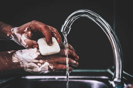 Guy washes his hands with soap under the faucet over a metal sink on  black