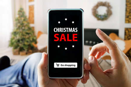 Christmas online shopping with phone. man sits in an apartment and makes purchases through a smartphone in an online store. Christmas tree, gifts, lights and decorations on background.