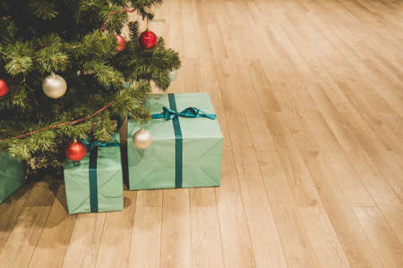 Christmas tree with decorations and presents under it interior. Blue box on the floor under the Christmas tree. Gifts from Santa Claus Packed in a festive wrapper