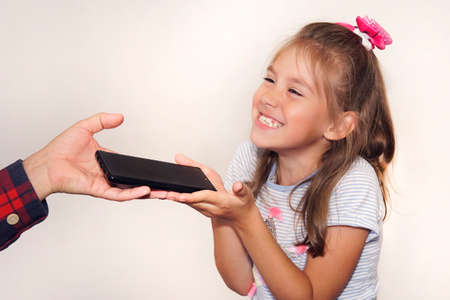 A father gives a gift to his daughter on her birthday. A man's hand passes a black new smartphone to the girl in close-up. A happy child grabs the phone in his hands. Stock Photo