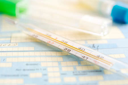 A thermometer on a table against the background of a medical document. a symptom of a coronavirus or flu