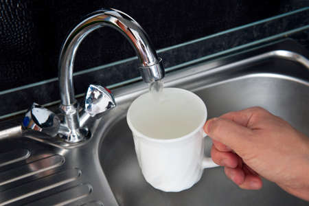 filling water in white porcelain glass at kitchen sink. clean filtered water flows from the tap. Danger of untreated drinking water.