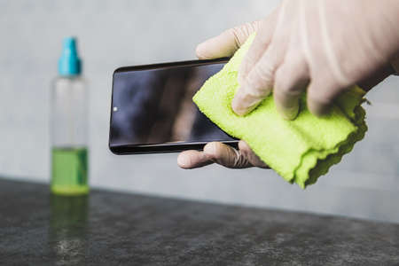 man wipes his mobile phone with rag. Disinfecting alcohol solution for killing germs on gadgets. method of protection against infections of viruses and microbes. Disinfection of mobile smartphone.