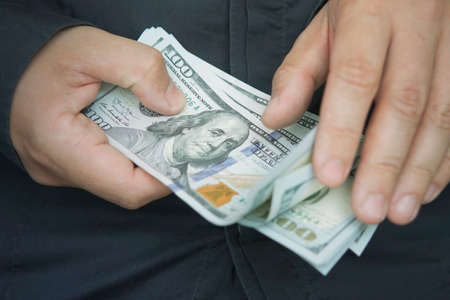 counting. money with hands. A male employee counts the salary in dollars, close-up. Cash for pocket expenses. Tips in 100 bills.