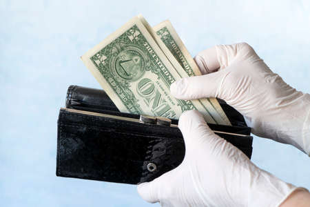 woman taking money out of female wallet wearing rubber gloves to prevent the spread of bacterias or viruses, take shopping during coronavirus pandemic. Microbes on money. Refusal of cash. concept