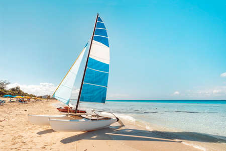 A sailing catamaran is parked on the white sand on the seashore against the backdrop of beautiful tropical nature. tourist attractions in Cuba. Archivio Fotografico