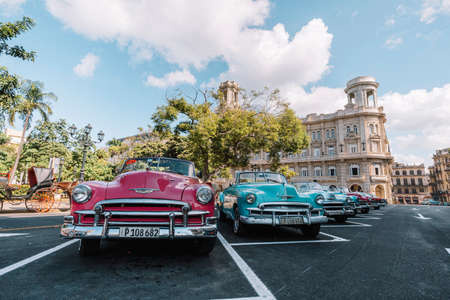 November 26, 2019, Havana, Cuba. Classic retro cars in different bright colors are parked in front of the national Museum of fine arts on the square, near the monument to Jose Marti 新聞圖片