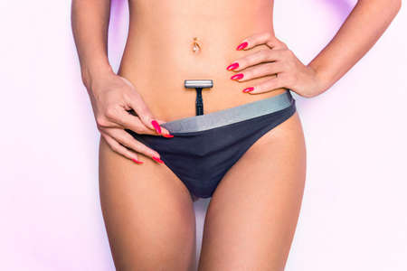 Woman with panties shave her pubic hair on pink background. shaving machine in panties. girl health and intimate hygiene. hair removal