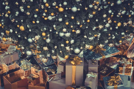 christmas, holidays, presents, new year and celebration concept - close up of gift boxes under x-mas tree on wooden floor.