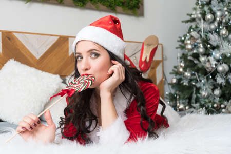 Sensual young woman biting a candy cane. The girl in the red suit Santa is looking dreamy in window lying on the bed and takes in his mouth a Lollipop on a stick.