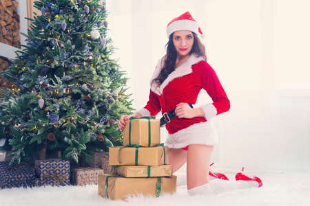 Beautiful young woman in Santa Claus looking at the camera clothes over Christmas background in bright morning light from the window. New year and Christmas celebration concept.