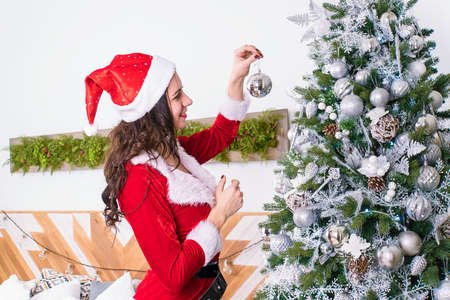 sexy women in the clothes of Santa Claus holding Christmas ball for Christmas tree. sexy girl decorates the flat to celebrate the new year and Christmas in bedroom with modern design