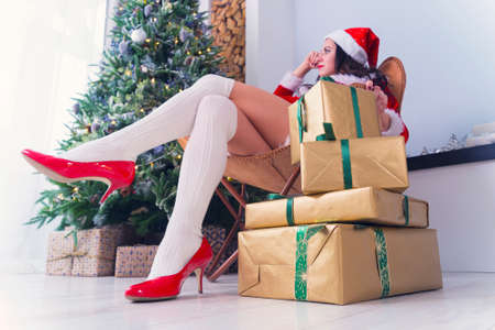 pretty girl sits in a chair near the festive Christmas tree, lots of gifts on the floor, Christmas morning. A large mountain of Christmas gifts wrapped in yellow gold paper and green ribbon.
