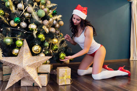Holidays and celebration concept - Happy brunette woman in santa's hat decorates a christmas tree at home in the living room, red pants 版權商用圖片