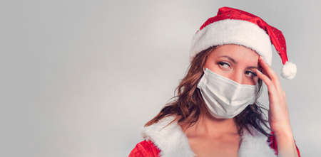 Beautiful young woman in red Santa Claus costume and protective medical mask against virus. Concept of celebrating Christmas in covid 19 pandemic and quarantine. Mrs. Santa sick covid. copy space