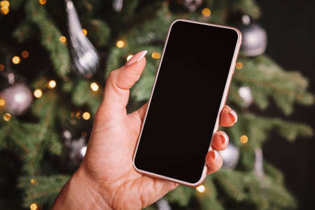 Smartphone in womans hand on the background of a Christmas tree. Empty space on the screen for design and text.