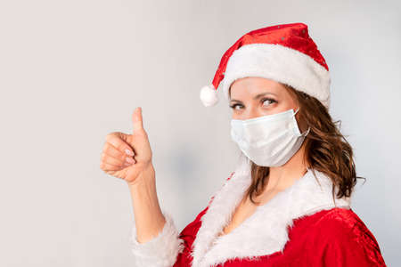 Beautiful young woman in red Santa Claus costume and protective medical mask against virus. Concept of celebrating Christmas in covid 19 pandemic, quarantine. Mrs. Santa happily shows a thumbs up Stock Photo