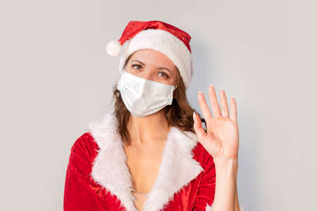 Beautiful young woman in red Santa Claus costume and protective medical mask against virus. Concept celebrating Christmas in covid 19 pandemic and quarantine. Mrs. Santa wave his hands