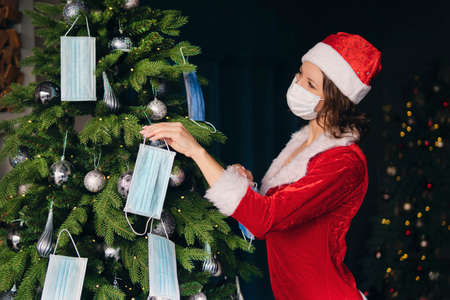 A young woman in a red Santa Claus costume decorates the Christmas tree with medical masks. The concept of celebrating new year and Christmas under coronavirus restrictions. holiday in quarantine