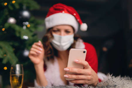 beautiful girl meets Christmas, New Year through a video call with friends. Quarantine. Self-isolation. Coronavirus 2020. miss Santa in a red suit holds a white smartphone in her hand reads message