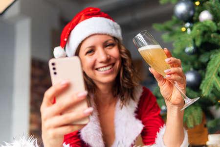 Closed up beautiful woman hat and red Santa Claus smiling happily, champagne glass, concept holiday celebrating, Christmas tree background. Christmas greetings online. New year's in quarantine.