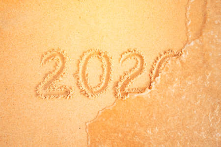 2020 written in sand, on tropical beach. The concept of year change. sea wave washes away the inscription. Celebration of new year holidays in warm countries. 版權商用圖片