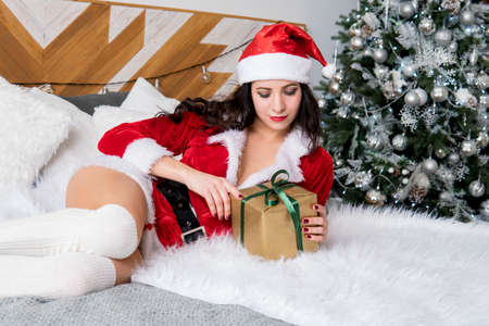 Surprised young woman opening Christmas gifts on the bed in the morning at home