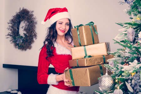 Curious young Santa girl, Christmas hat holding box with gift present on gray wall background. Happy New Year celebration holiday party concept.
