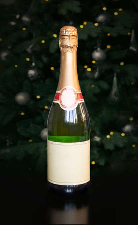 gold bottle of champagne on black background of a decorated Christmas tree for your christmas or new year project. Empty space for the design or text on the label.